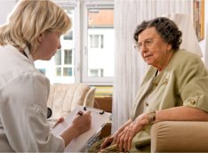 caregiver writing notes while talking to the elderly woman